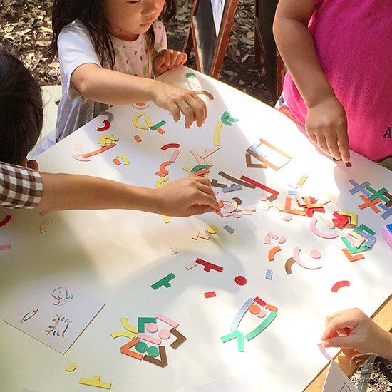 カラーフルなピースをならべて、絵や文字をつくる。子どもも大人も手を動かして気の向くまま。描くように、書くように楽しむ、それがエモージ。